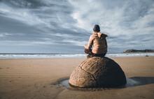 A Man Sitting On The Rock At Moeraki Boulder Beach In New Zealand.