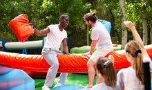 Laughing African American Man Fighting By Pillows With His Friend While Sitting On Inflatable Beam On Adults Bouncy Playground..