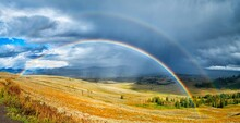Rainbow Over A Beautiful  Green And Yellow Field Under The Cloudy Sky