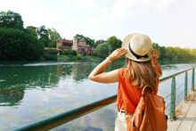 Traveler Girl Holding Her Hat Discovering Hidden Castle In The Park. Young Woman Relaxing And Breathing On Promenade River.