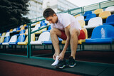 Portrait of young Caucasian man, male athlete, runner isolated at public stadium, sport court or running track outdoors. Summer sport games.