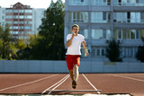 Young Caucasian man, male athlete, runner practicing alone at public stadium, sport court or running track outdoors. Summer sport games.