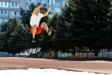 Young Caucasian sportive man, male athlete, runner jumping high at public stadium, sport court or running track outdoors. Summer sport games.