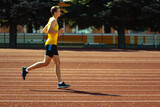Young Caucasian sportive man, male athlete, runner jogging at public stadium, sport court or running track outdoors. Summer sport games.