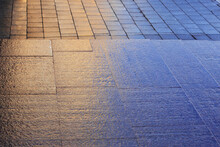 Big City Pavement After The Rain. Wet Granite Surface With Colorful Light. Orange And Blue Textured Background.