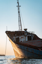 Old Abandoned Rusty Boat Against The Blue Sky