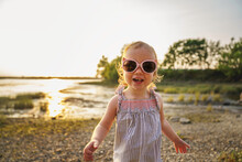 Baby Outdoors Enjoying Nature On The Sunset Beach With Sunglasses