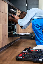 Hardworking Afro American Guy In Blue Workwear Repairing Broken Electric Oven In Kitchen At Home Indoors, Using Worktool. Side View Portrait. Handyman Is Concentarted On Repair Process