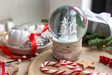 Christmas Decorations, A Snow Globe And Presents And Star Shaped Biscuits.
