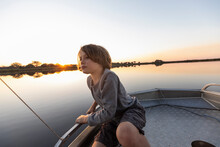 A Young Boy Fishing From A Boat On The Flat Calm Waters Of The Okavango Delta At Sunset