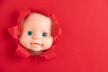 The Doll's Face Peeks Out From Behind Pieces Of Red Paper, Close-up. Copy Space.