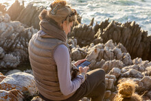 Woman Sitting On Rocky Shore, Looking At Her Mobile Phone.