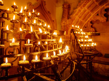 Lit Candles In Racks In A Historic Church