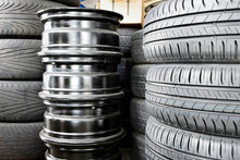 Stack Of Car Tyres And Wheel Rims In An Auto Repair Shop Garage.