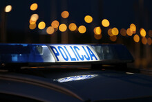 Sygnalizator Błyskowy Niebieski Na Dachu Radiowozu Policji Polskiej W Nocy.