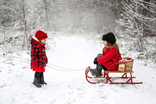 The Girl Is Taking Her Sister On A Sled With Gifts In The Forest On A Frosty Snowy Day Among Bushes And Trees. Looking Forward To The New Year And Merry Christmas. Red And Black Checkered Clothing