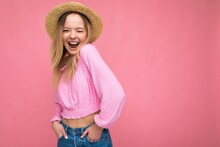 Beautiful Young Blonde Woman Smiling And Having Fun Standing Isolated Over Pink Wall Keeping Hands In Pockets Winking Wearing Pink Blouse And Summer Hat