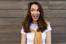 Portrait Of Successful Smiling Joyful Happy Young Brunet Woman Wearing Casual White T-shirt And Jeans With Yellow Sweater Poising Near Brown Wall In The Street And Having Fun