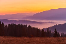 Beautiful Autumn Sunrise In The Mountains. Fog Spreads In The Lowlands In October