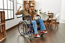 Young Hispanic Girl Sitting On Wheelchair At Home Very Happy And Excited Doing Winner Gesture With Arms Raised, Smiling And Screaming For Success. Celebration Concept.
