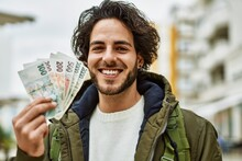 Handsome Hispanic Man Holding Czech Crown Banknotes At The City