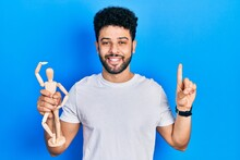 Young Arab Man With Beard Holding Small Wooden Manikin Smiling With An Idea Or Question Pointing Finger With Happy Face, Number One