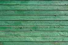Green Old Cracked Paint On A Wooden Surface. Background From Wooden Boards With Peeling Paint Top View.