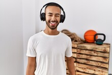 African American Man Listening To Music Using Headphones At The Gym Winking Looking At The Camera With Sexy Expression, Cheerful And Happy Face.