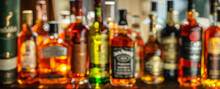 Beautiful Bokeh From A Row Of Alcoholic Bottles In Backlight.