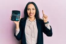 Young Hispanic Girl Showing Calculator Device Smiling With An Idea Or Question Pointing Finger With Happy Face, Number One
