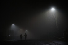 Two Mysterious Hooded Men Walk Away Down A Dark Foggy Road, Dimly Lit