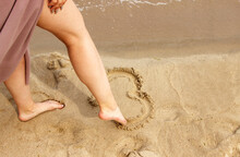 Woman Draws With Her Foot Heart On The Sand By Sea