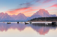Overview Of Jackson Lake With Colorful Boats In Foreground Before Sun Rise Viewing From Signal Mountain Campground At Grand Teton National Park, Wyoming USA.