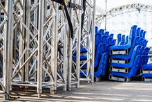 Mobile Concert Stage Prepared For Assembly And Installation On The Street. Metal Structure With Disassembled Plastic Seats. Close-up