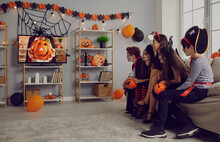 Kids In Spooky Costumes Of Witches, Pirates And Vampires Together Watching Children's Halloween Movie Sitting On Sofa In Interior With Festive Orange Black Pumpkin Decor At Fancy Dress Party At Home