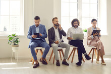 Multiethnic Young Employees Sit On Chair In Row In Company Office Get Ready For Interview In Corporation. Motivated Diverse Applicants Candidates Prepare For Recruitment Talk Using Device Gadgets.