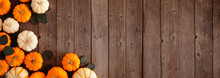 Fall Corner Border Of Pumpkins And Eucalyptus Leaves Against A Rustic Dark Wood Banner Background. Above View With Copy Space.