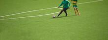 Dois Jogadores A Jogar Futebol E A Disputar A Posse De Bola - Equipamentos Verde E Preto E Amarelo E Verde - Casaco Vestido