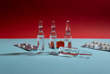 Glass Ampoules And Pills In Blister Pack On Blue And Red Background