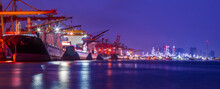 Panorama Image Of Container Cargo Ship With Ports Crane Bridge Loading Dock To Terminal In Harbor Against Refinery Industrial At Twilight