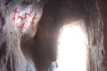 Ancient Paintings On The Stone Cave.in Concept A Light At The End Of The Tunnel. A Concept Image Representing Hope, Faith Of Humanity