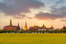 Grand Architecture, A Venue Now Mostly Used For Ceremonial Events. The Buddhist Temple Of The Wat Phra Kaew Temple At The Grand Palace In Sunset Sky On Grass Park In Bangkok, Thailand