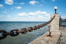 Iron Chain Fencing On The Pier On The Sea Water Background.