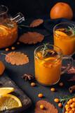 Fototapeta Kawa jest smaczna - Autumn hot tea with sea buckthorn berries, orange, cinnamon and rosemary in glass cups and teapot on dark background