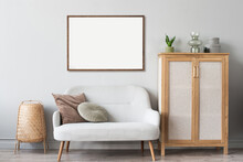 Blank Picture Frame Mockup On Gray Wall. Artwork In Interior Design. View Of Modern Scandinavian Style Interior With Sofa And Empty Canvas For Painting Or Poster On Wall. Minimalism Concept