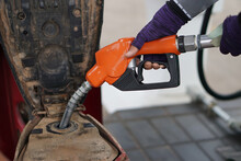 Closeup Of Hand Holds The Orange Petrol Pump Filling Nozzle To Fill Fuel Into Motorcycle. Refueling At A Gas Station In Thailand.