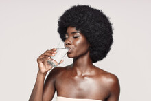 Portrait Of Beautiful Young African Woman Drinking Water While Standing Against Gray Background