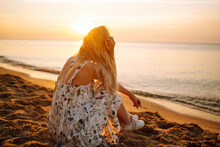 Young Woman Walks Along Seashore At Sunset. Travel, Weekend, Relax And Lifestyle Concept.