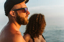 A Portrait Of A Handsome Guy With A Beard Wearing Sunglasses And Standing By The Sea. In The Background Is A Curly Girl