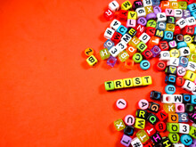 Colorful Alphabet Beads With Text TRUST On Red Background.